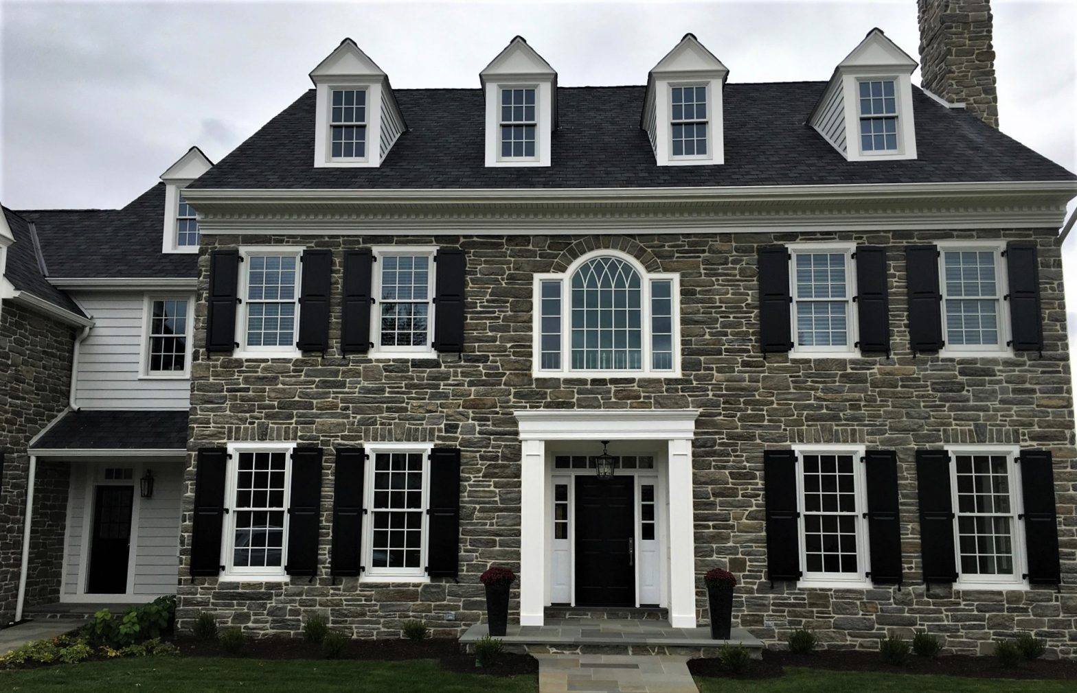Exterior of a stone home with new windows
