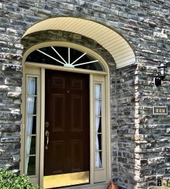 Exterior of a home with brown front door and stone siding