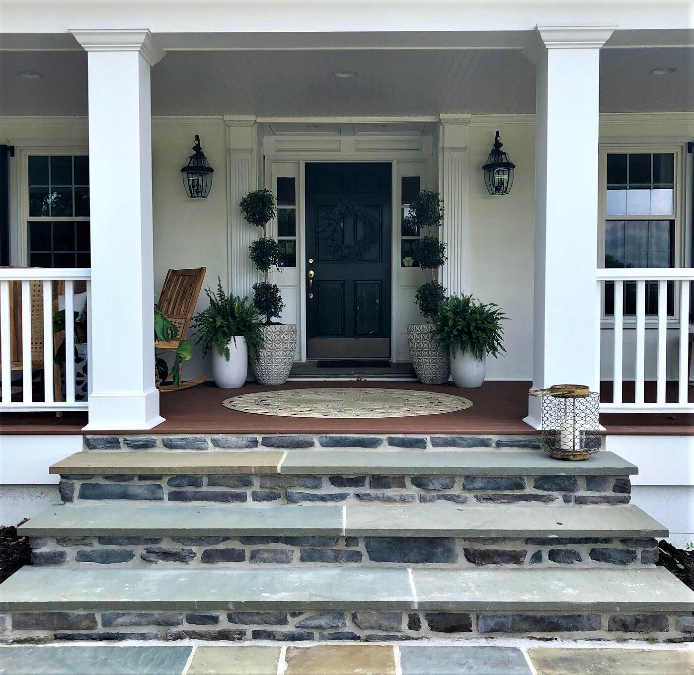 Stone steps leading up to the front door of a white house with porch columns