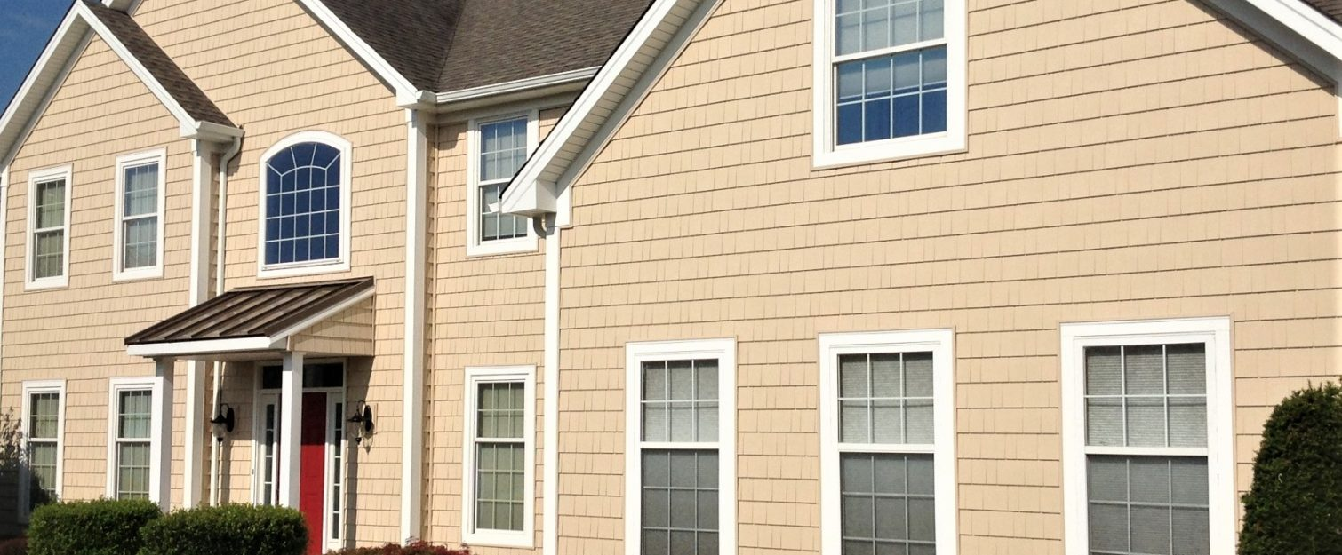 Exterior of home with tan shingle siding and white windows