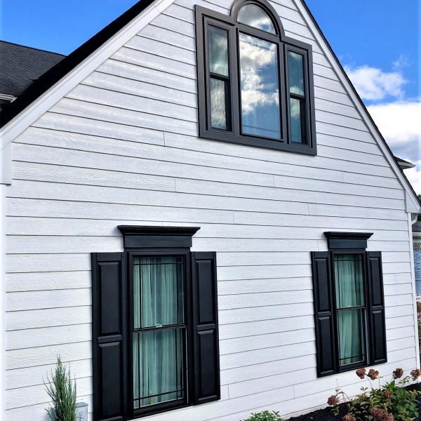 Side view of house with white siding and black windows with black shutters