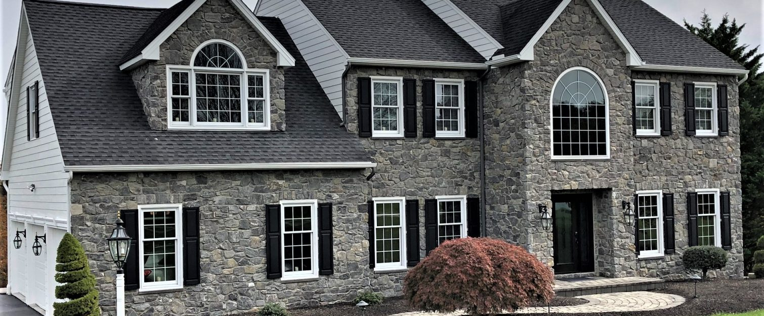 A large home with a stone exterior and white windows with black shutters