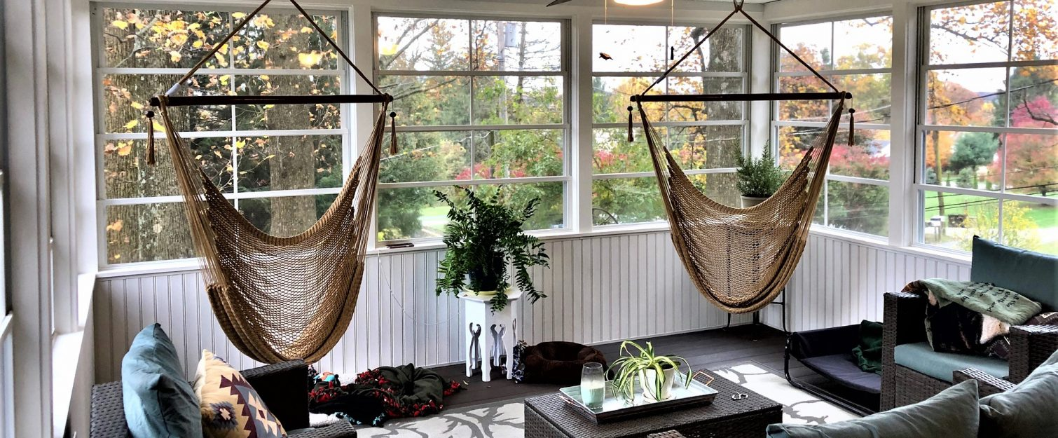 Interior of a three season room with two hanging hammock chairs