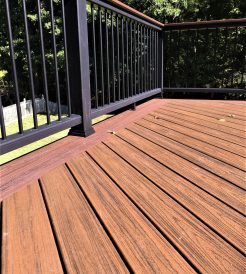 Closeup of a brown composite wood deck with black railing