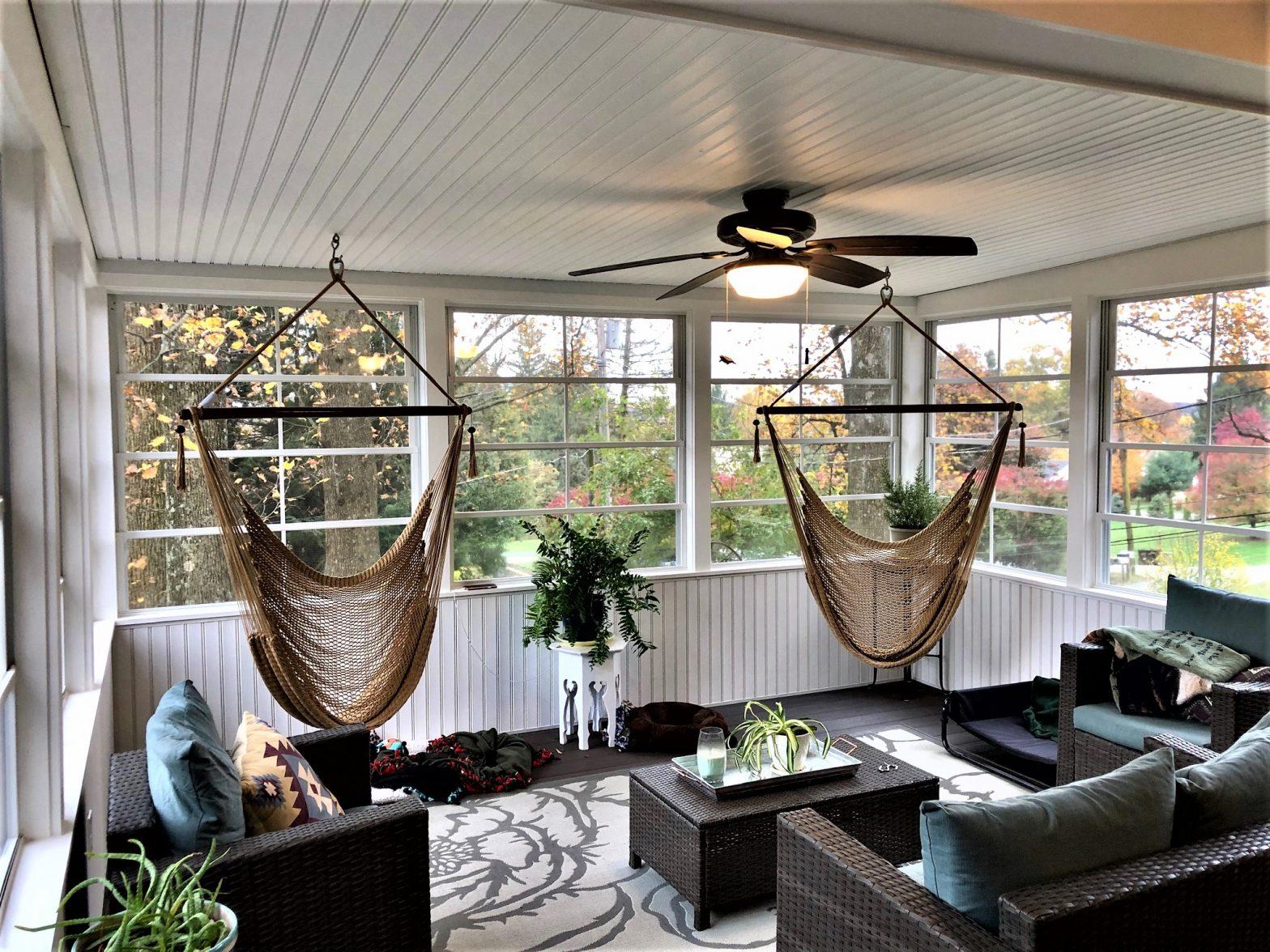 Sun room with 2 hammocks, a fan, and wicker furniture