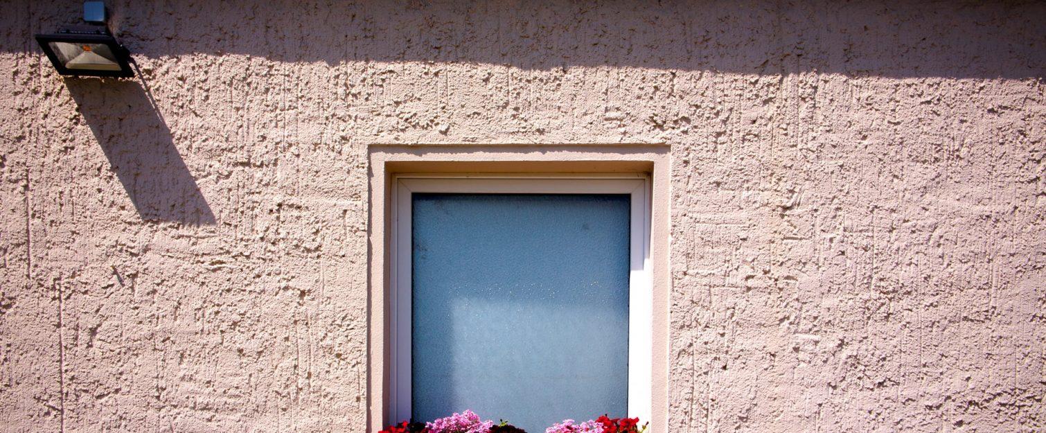 Window with flowers on a stucco house