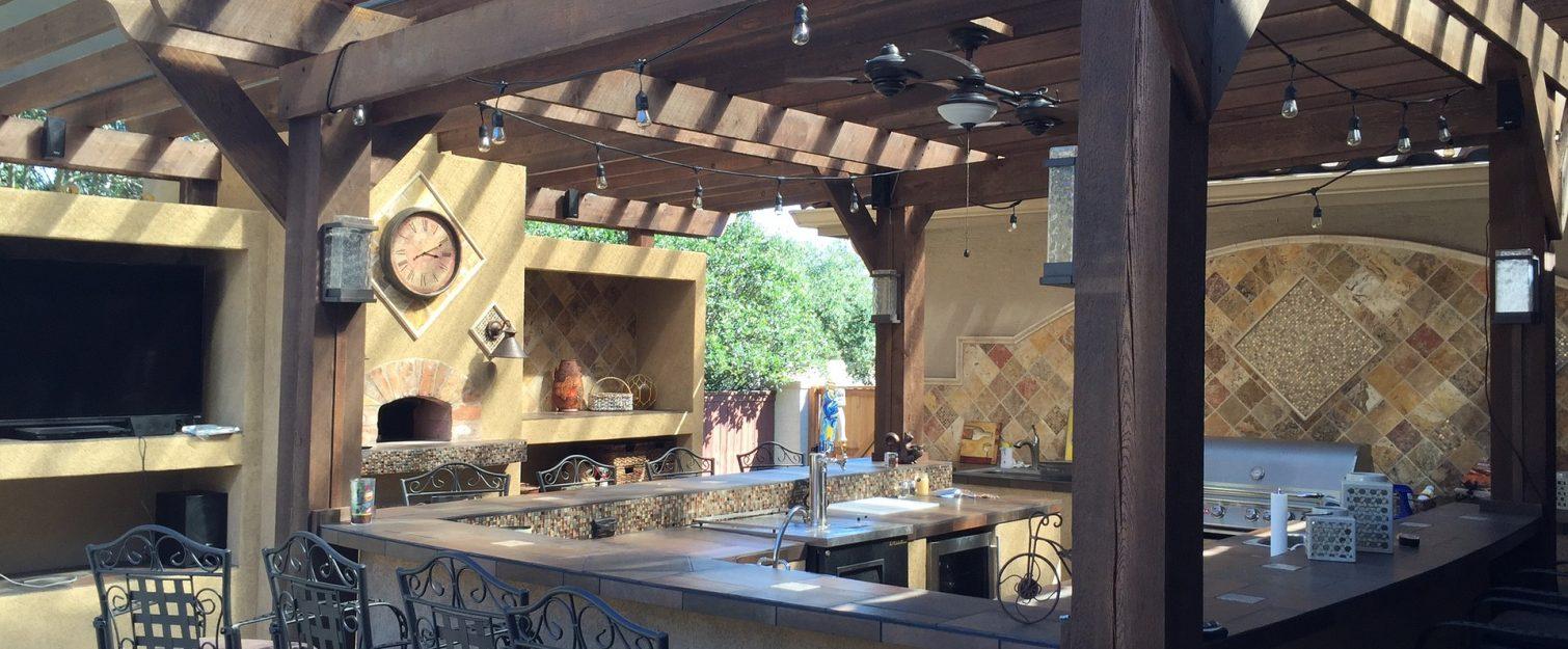 Dark brown pergola with lights covering a backyard bar