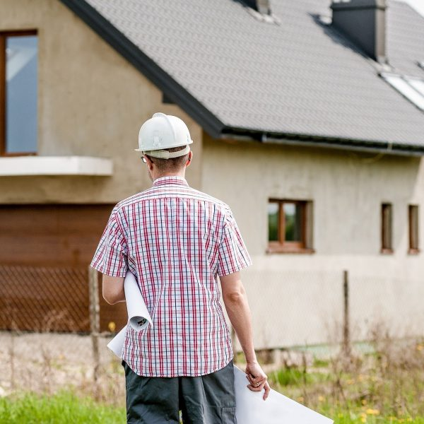Man with hard hat facing house